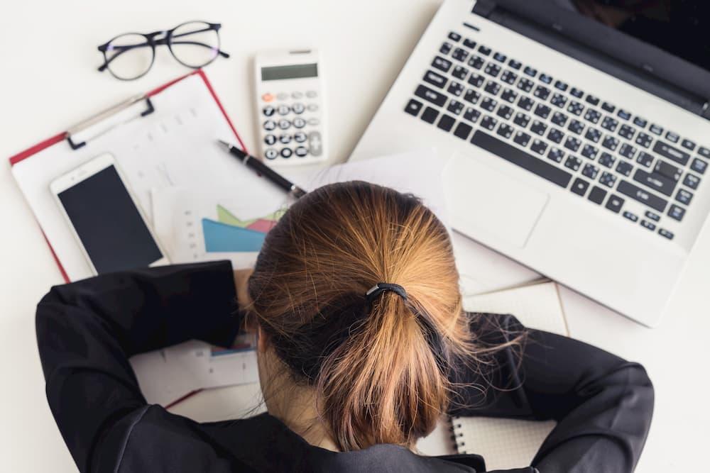 pessoa cansada na mesa, notebook, celular, calculadora.